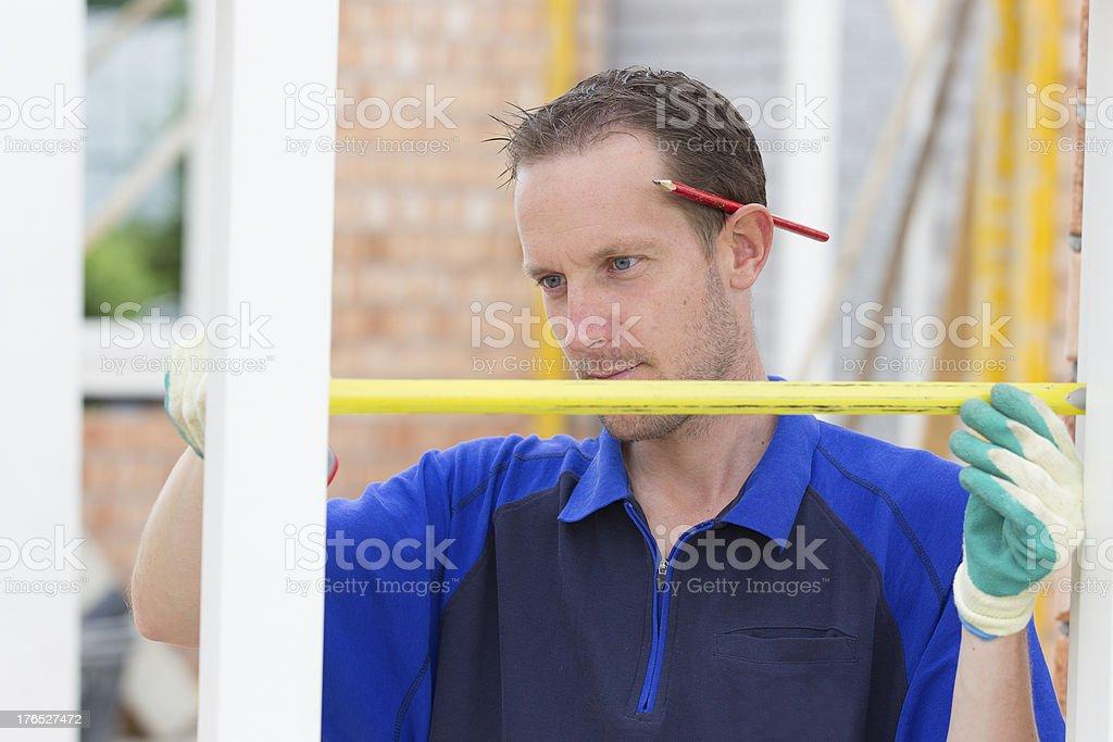 Carpenter measuring window frame royalty-free stock photo