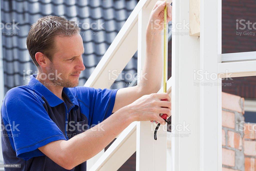 Carpenter measuring window frame stock photo