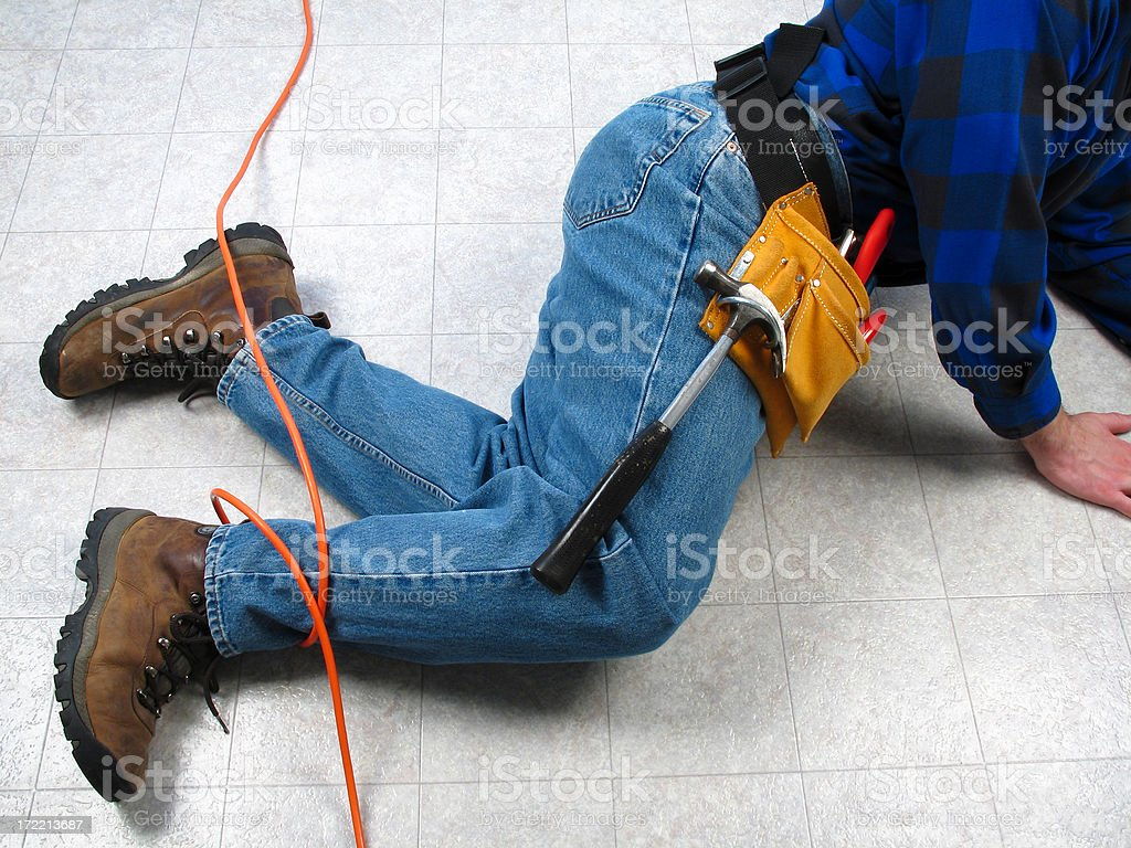 Carpenter or Construction Worker Tripping on Orange Extension Cord stock photo