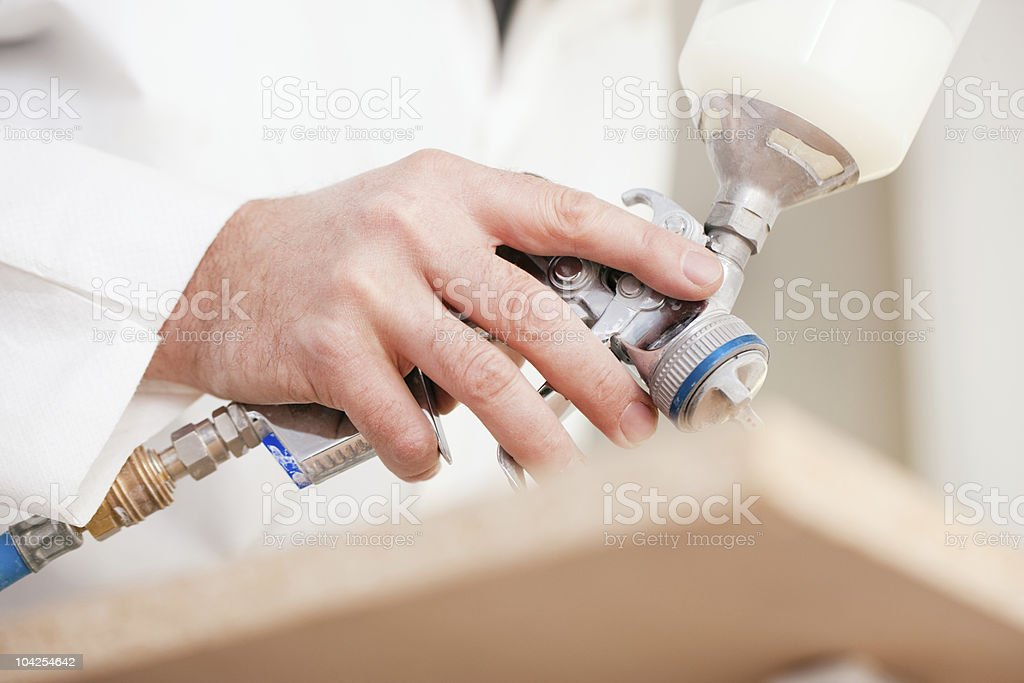 Carpenter painting wood with airbrush royalty-free stock photo