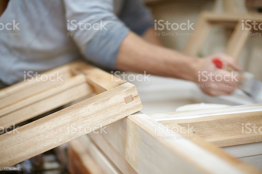 A carpenter painting wooden window frames stock photo