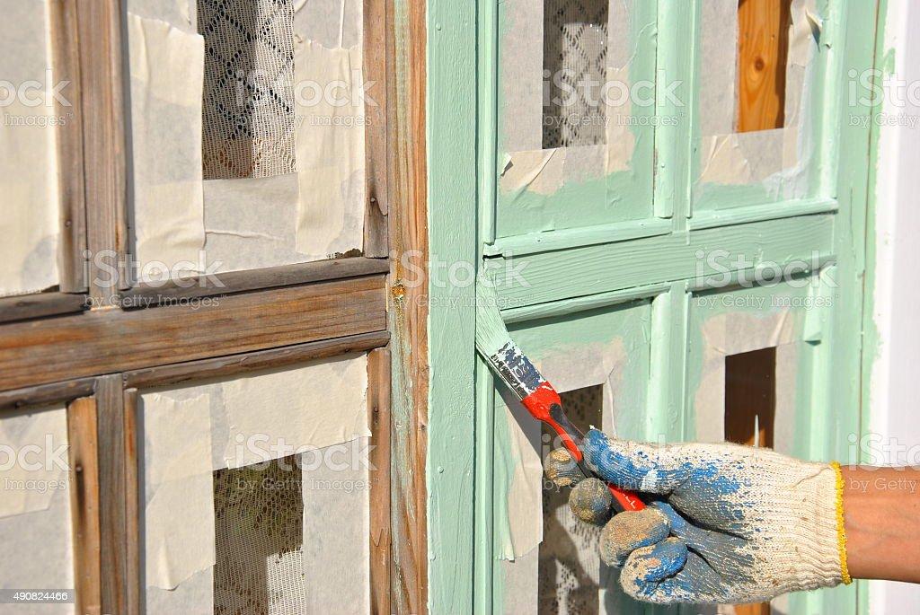 Carpenter paints wooden window stock photo