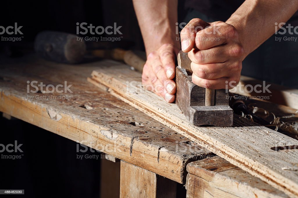 carpenter planing a plank of wood with a hand plane stock photo