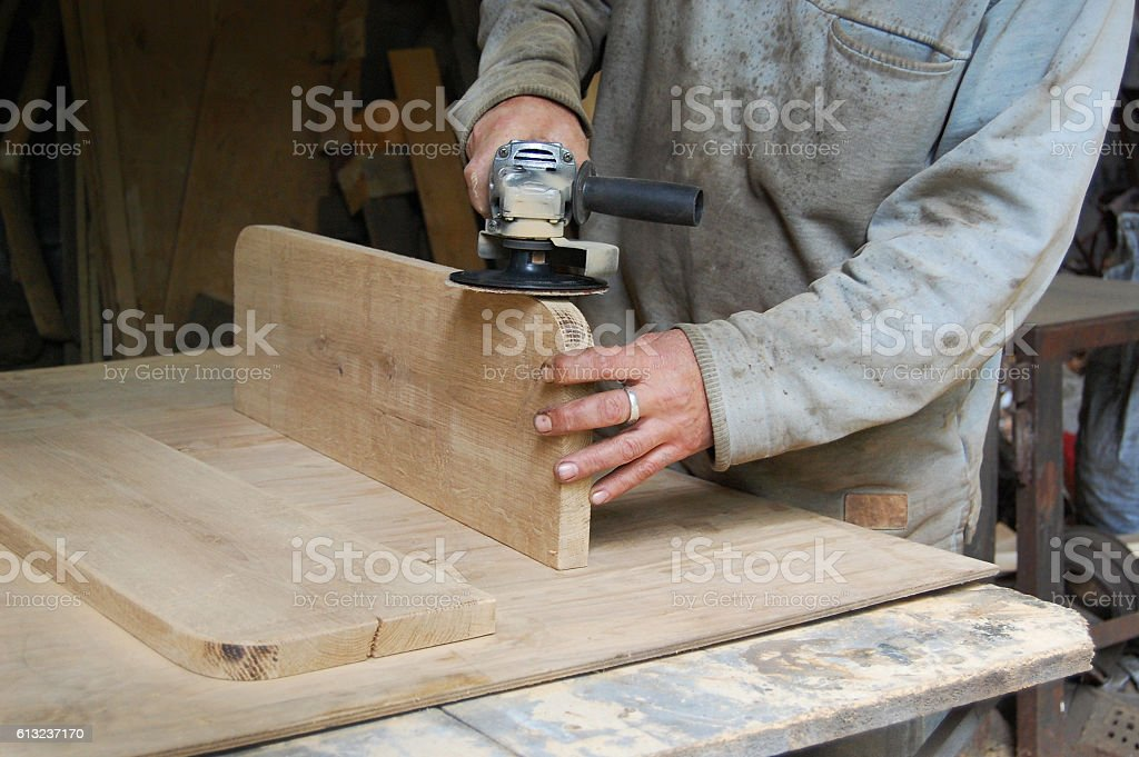 Carpenter polishing a wooden surface, hand and electrical polisher stock photo