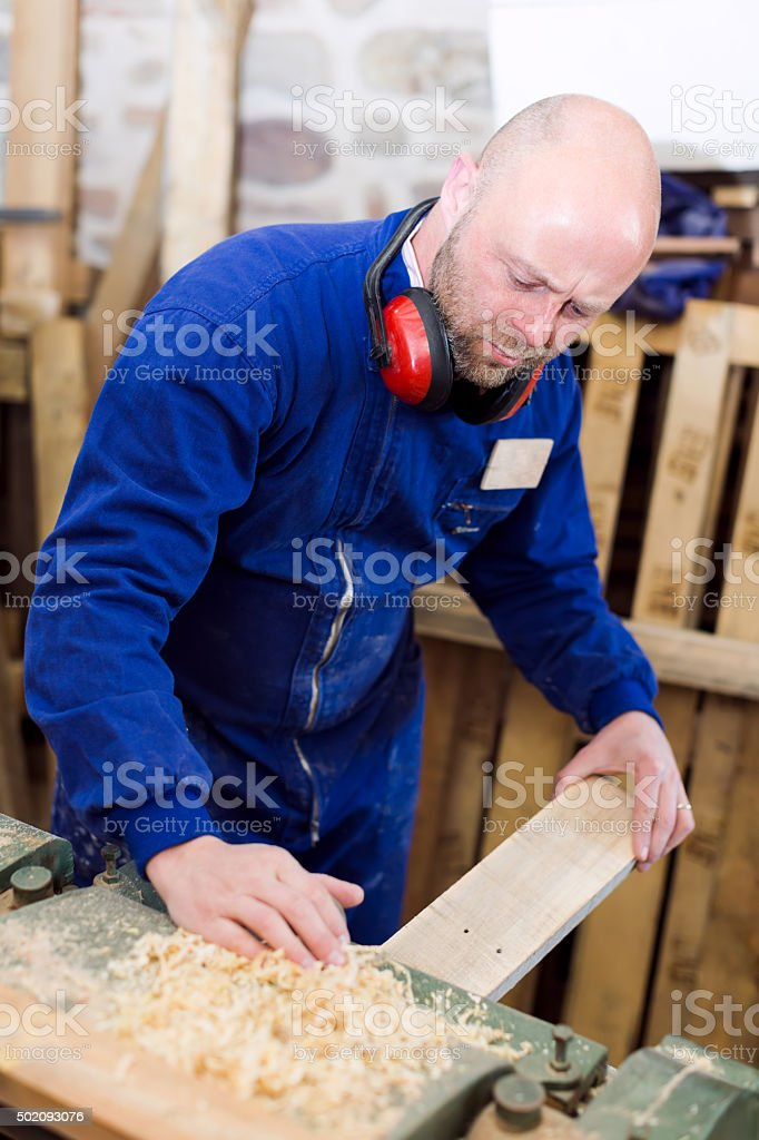 Carpenter processing a plank of wood stock photo