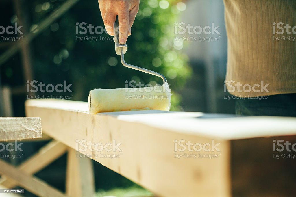 Carpenter protects the wood with clearcoat stock photo