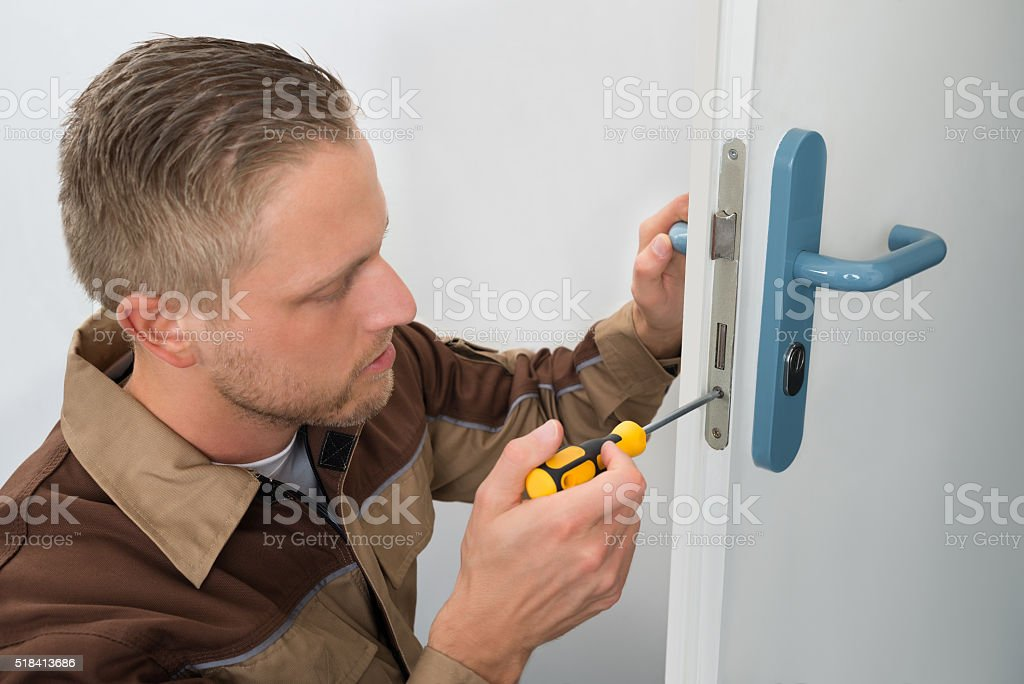 Carpenter Repairing Door Lock stock photo