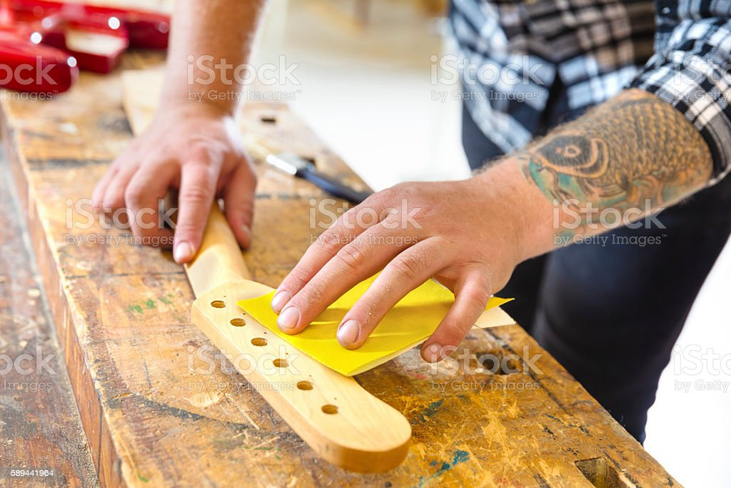 Carpenter sanding a guitar neck in wood at workshop stock photo
