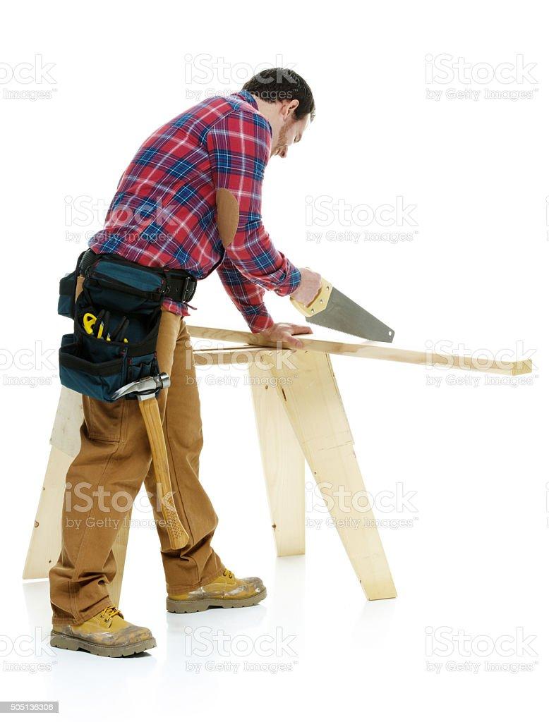 Carpenter sawing stock photo