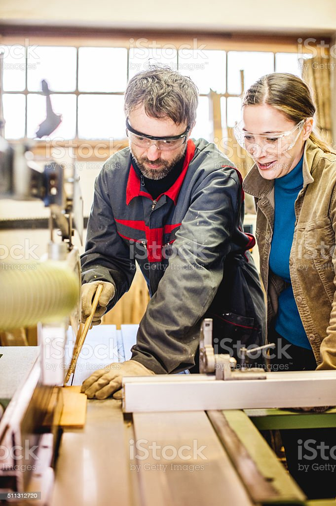 Carpenter Sawing Piece of Wood with Table Saw stock photo
