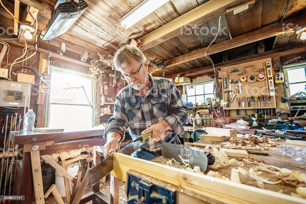 Carpenter sawing wood in his workshop stock photo