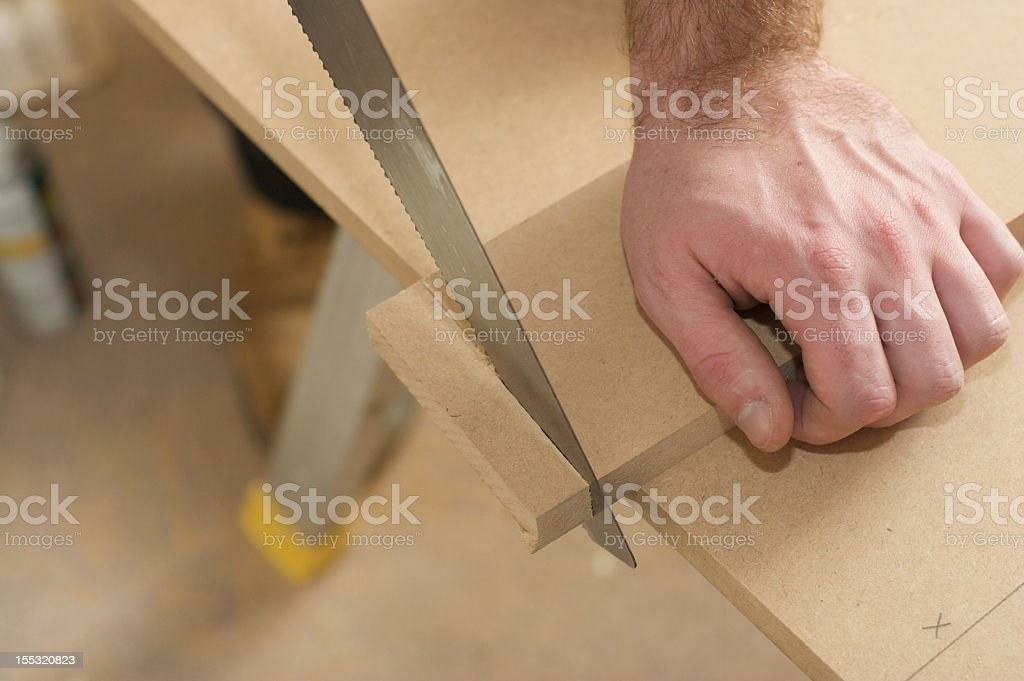 Carpenter Sawing  Wood in Workshop stock photo