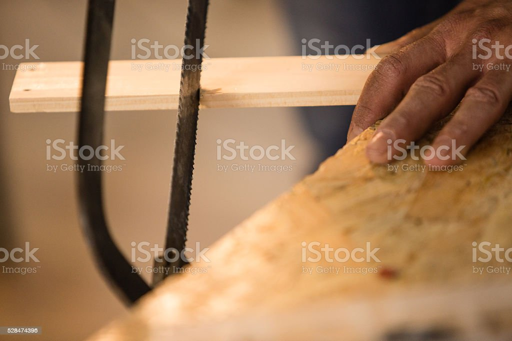 Carpenter sawing wood with hand saw.