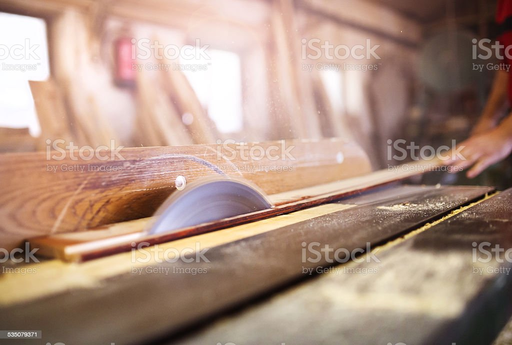 Carpenter sawing wooden planks stock photo