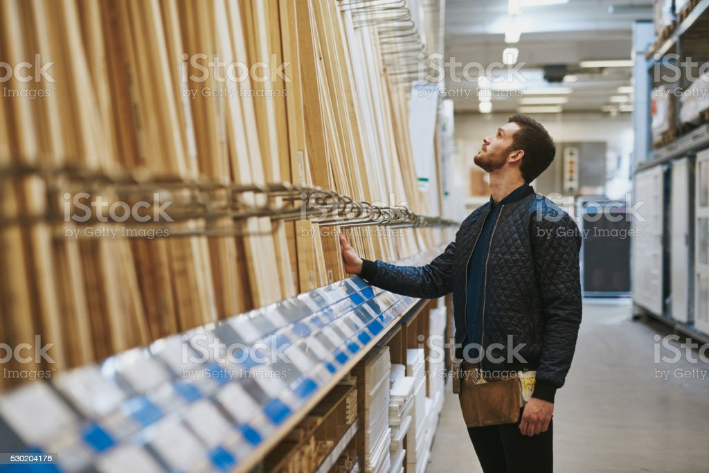 Carpenter selecting wood in a hardware store stock photo
