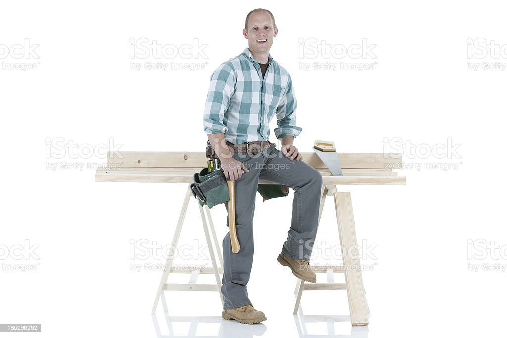 Carpenter sittiing on a sawhorse royalty-free stock photo