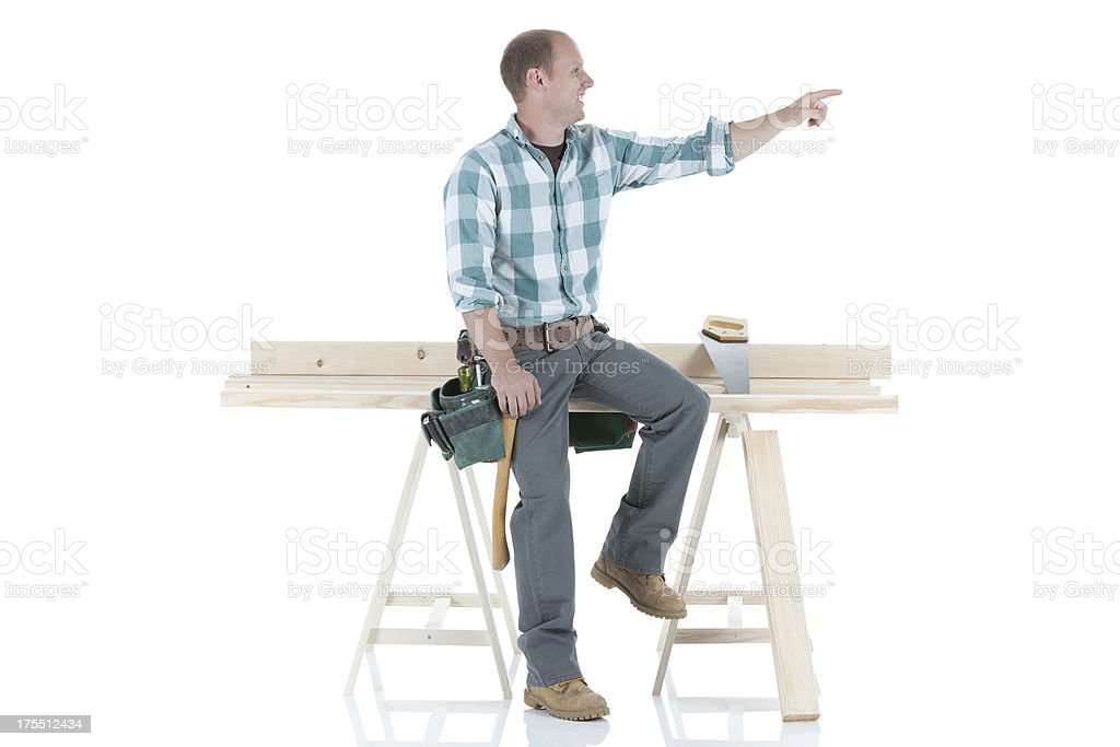 Carpenter sitting on a sawhorse and pointing away royalty-free stock photo