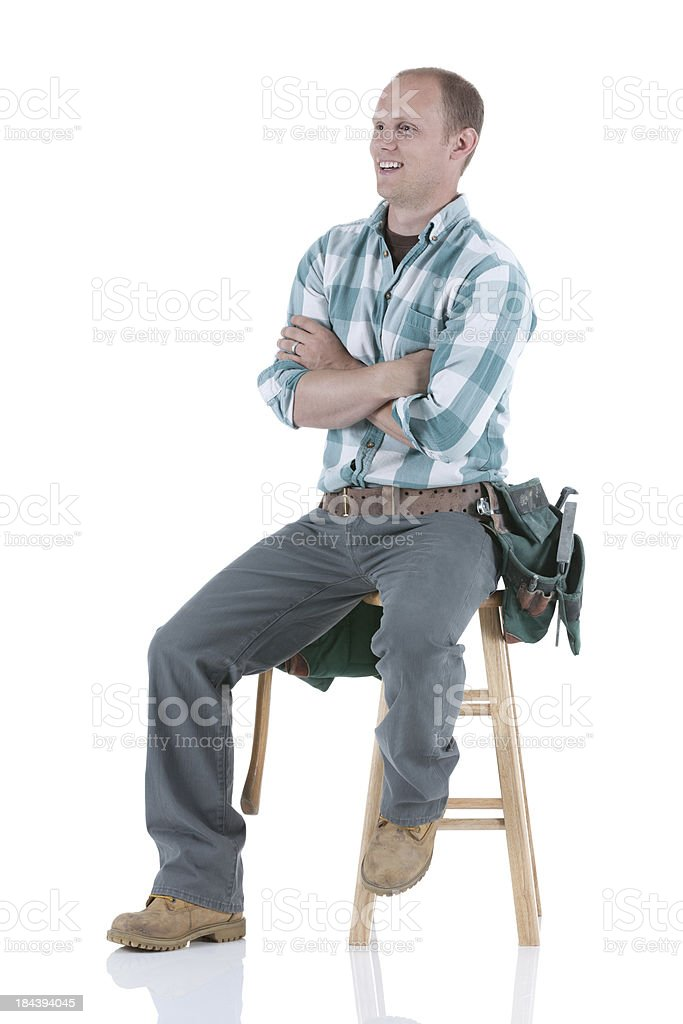 Carpenter sitting on a stool with his arms crossed royalty-free stock photo
