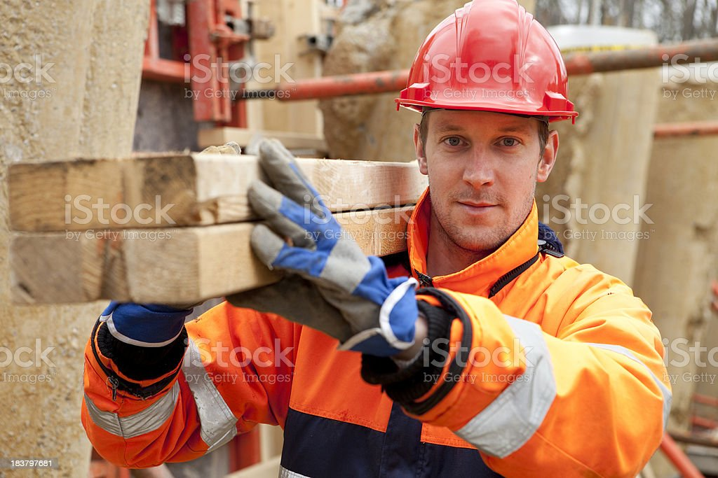 Carpenter smiling at construction site. stock photo