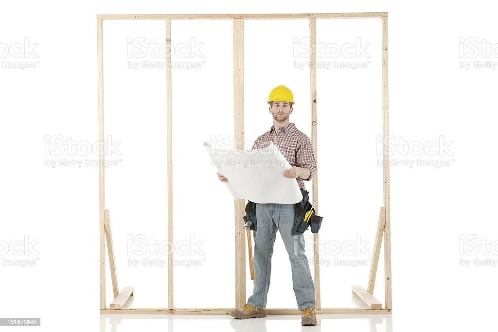 Carpenter standing in front of a wooden framework royalty-free stock photo