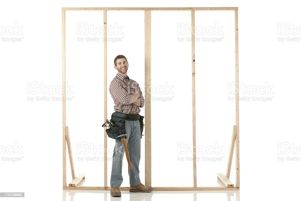 Carpenter standing near a wooden frame royalty-free stock photo