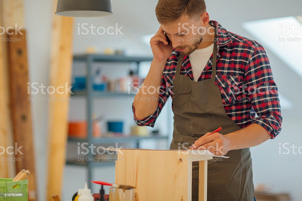 Carpenter talking on the phone in his workshop. stock photo