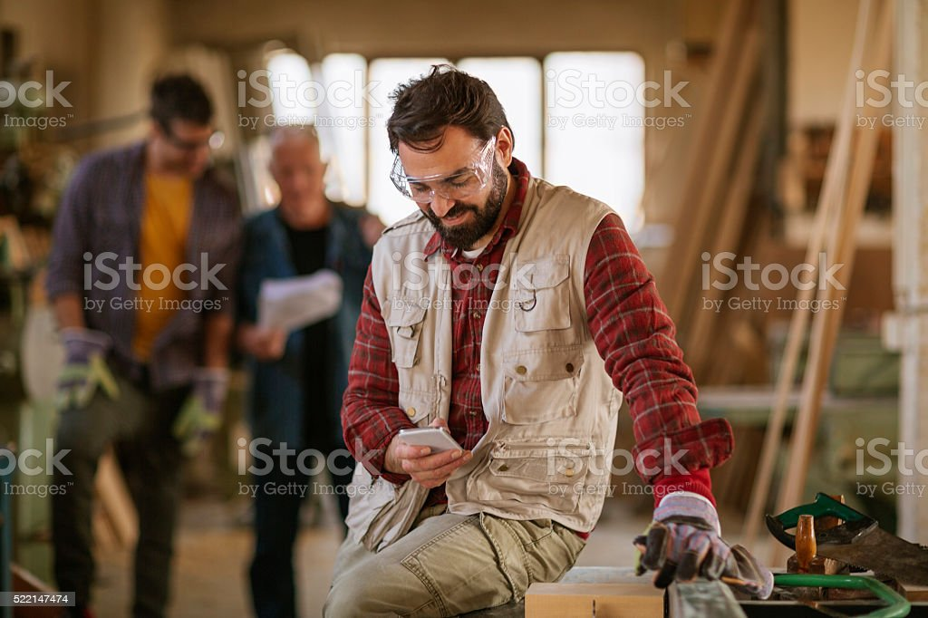 Carpenter texting while working stock photo