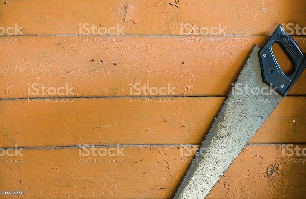 Carpenter tool Saw over wood plank. stock photo