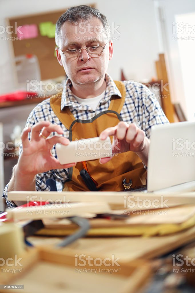 Carpenter use a mobile phone to take pictures. stock photo