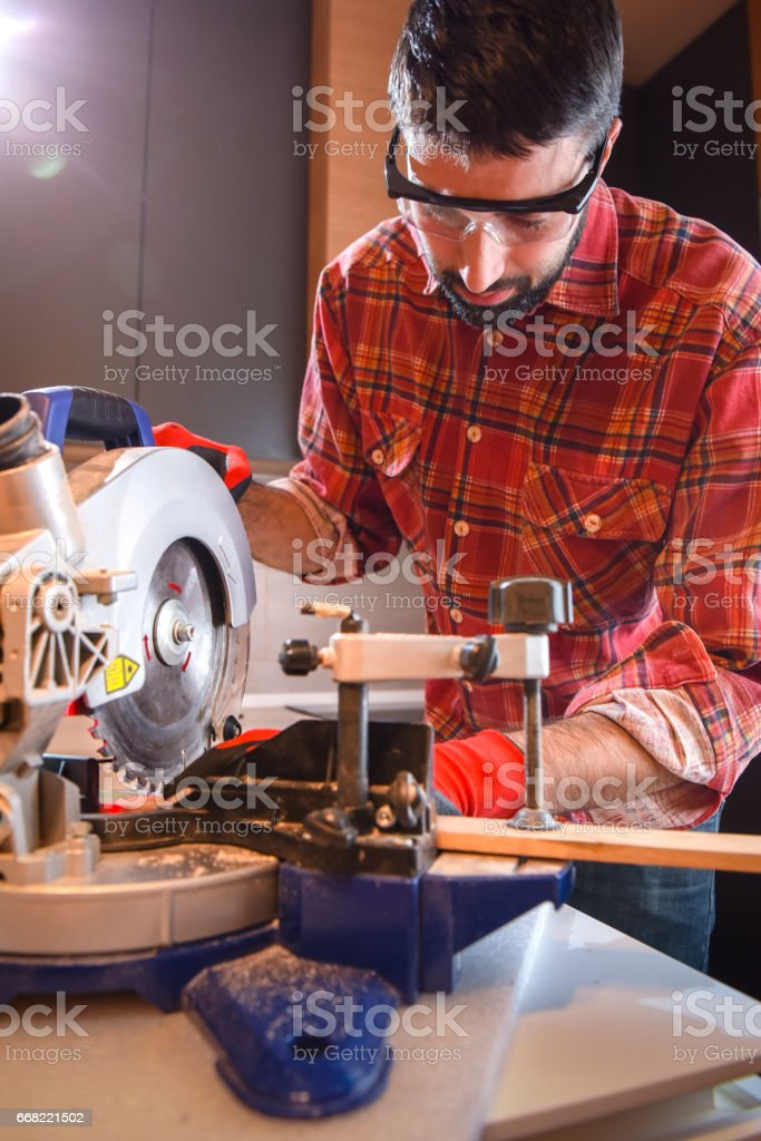 Carpenter use electric saw to cutting wooden plank stock photo