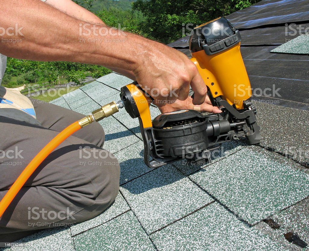 Carpenter uses nail gun stock photo