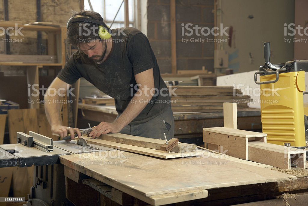 Carpenter Using An Electric Planer In Workshop stock photo