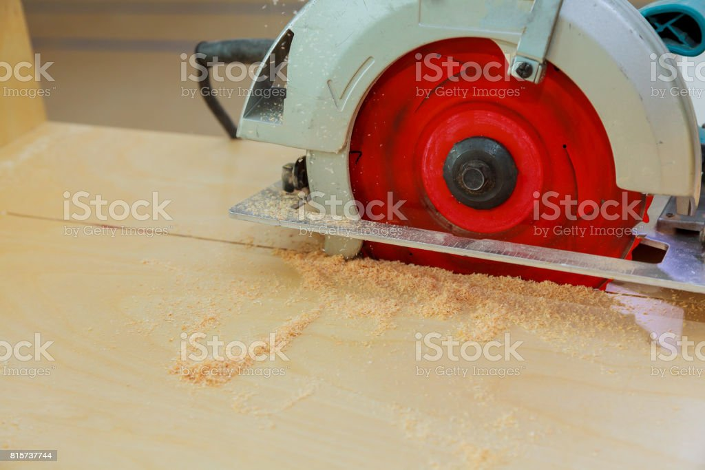 Carpenter using circular saw cutting wooden board in wood workshop. stock photo