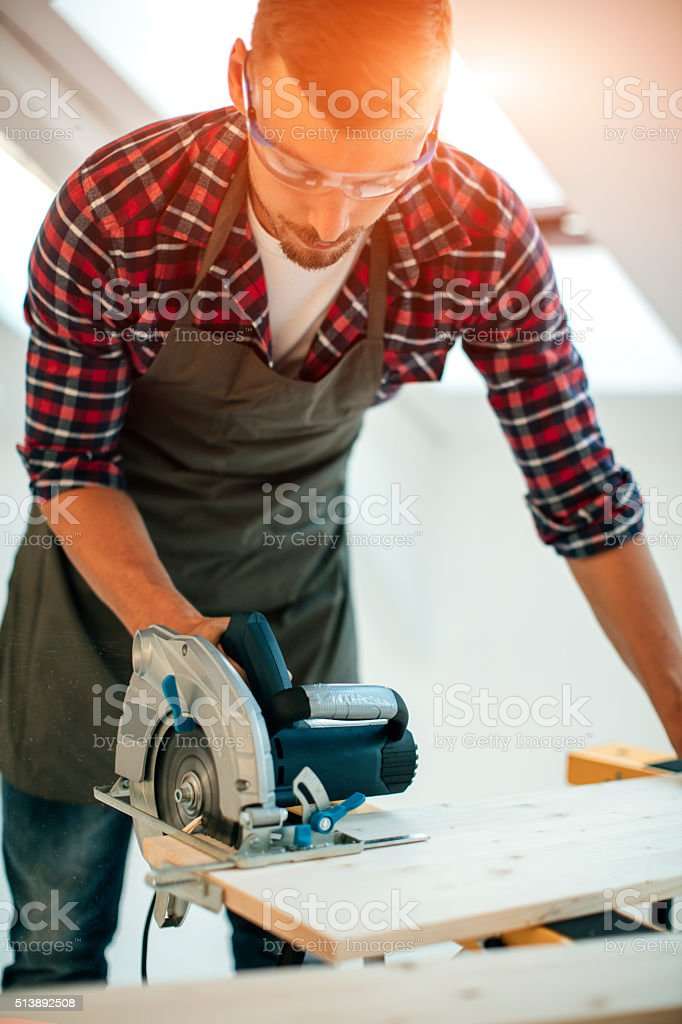 Carpenter Using Circular Saw In His Workshop. stock photo
