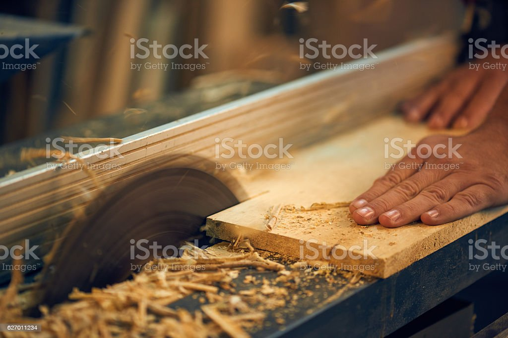 Carpenter using circular saw in workshop stock photo