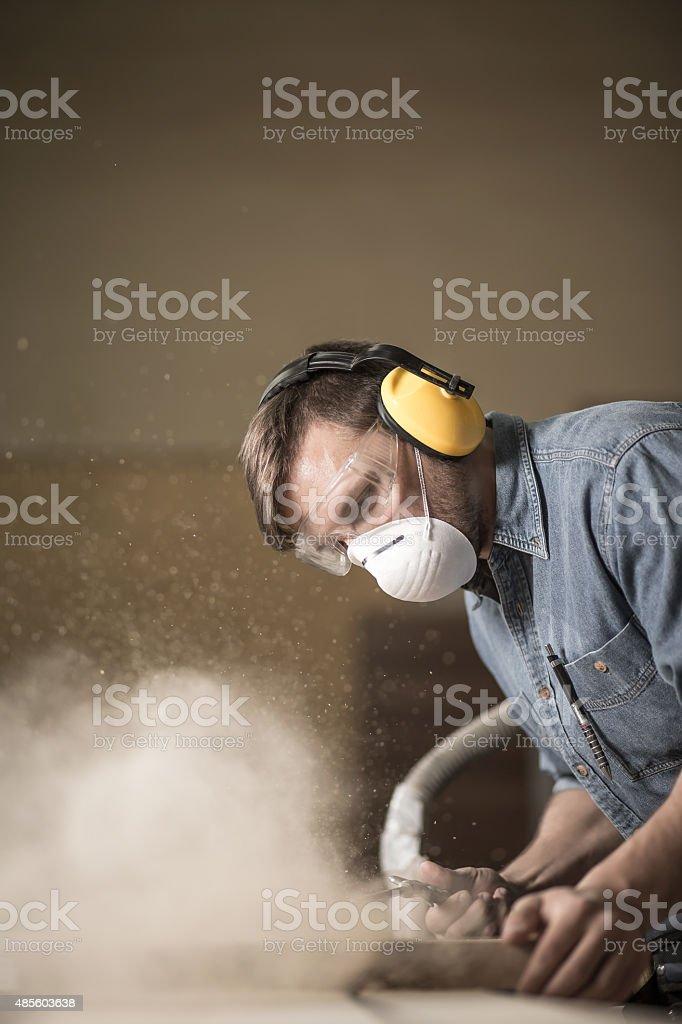 Carpenter using electric saw stock photo