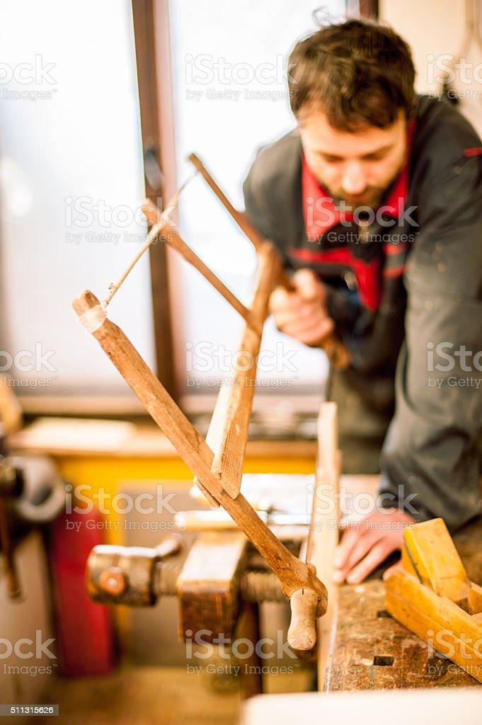Carpenter Using Hand Wooden Buck Saw stock photo