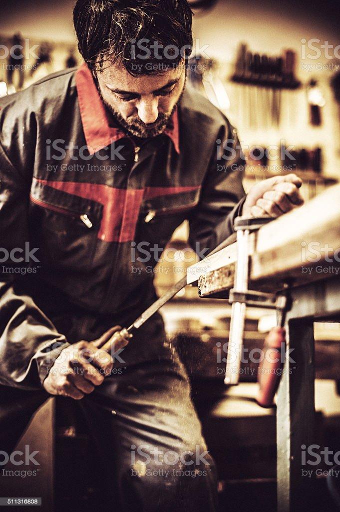 Carpenter Using Rasp at Woodshop stock photo