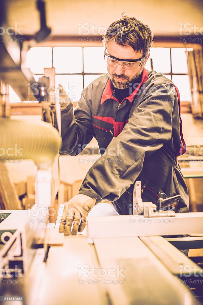 Carpenter Using Table Saw in Woodshop stock photo