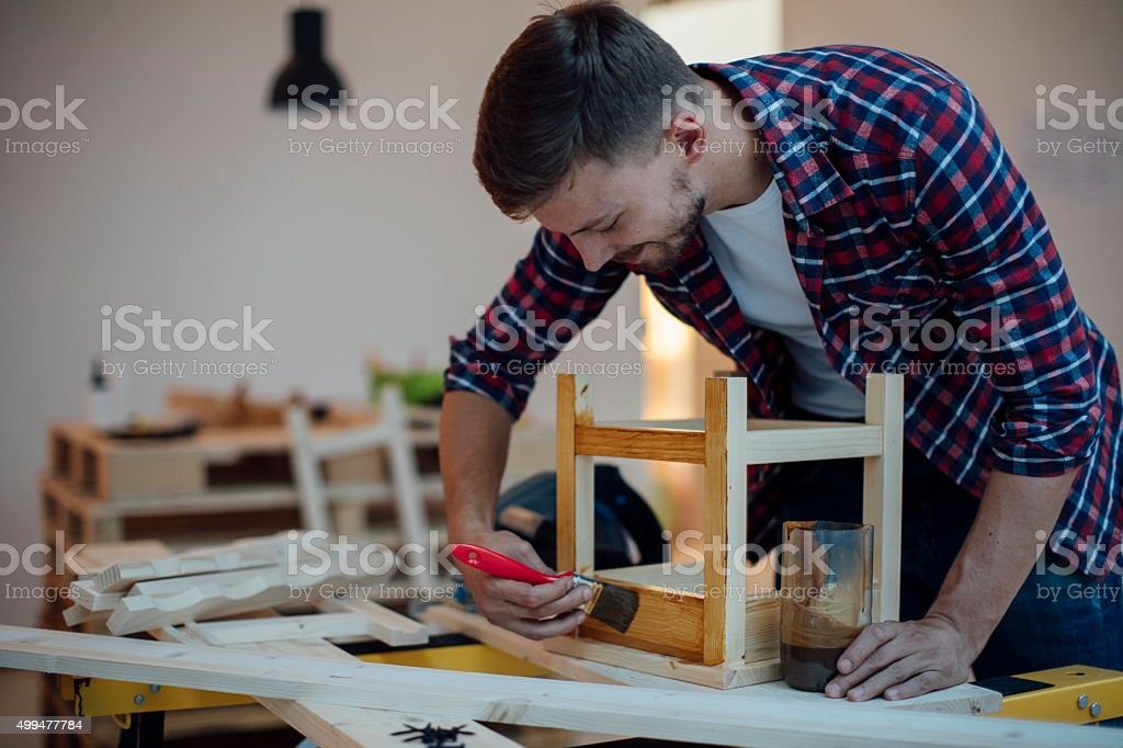 Carpenter Varnishing Furniture. stock photo