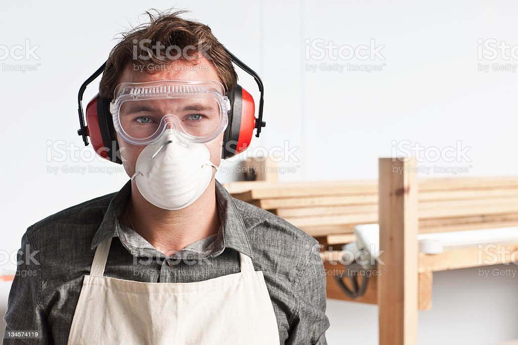 Carpenter wearing dust mask and ear defenders, portrait stock photo