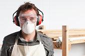 Carpenter wearing dust mask and ear defenders, portrait