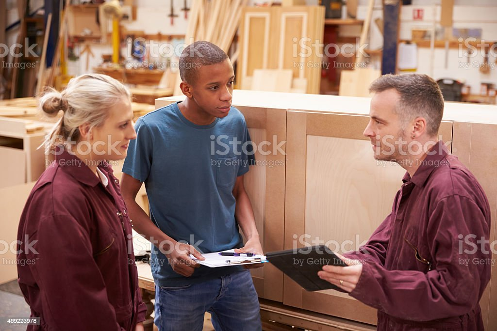 A carpenter with apprentices in a furniture workshop stock photo