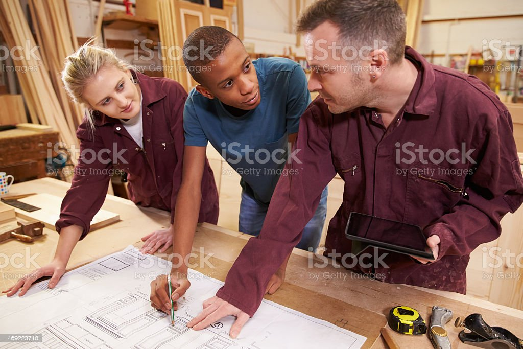 Carpenter With Apprentices Looking At Plans In Workshop stock photo