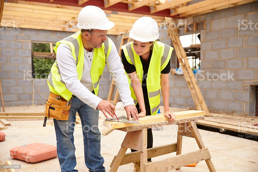 Carpenter With Female Apprentice Working On Building Site stock photo