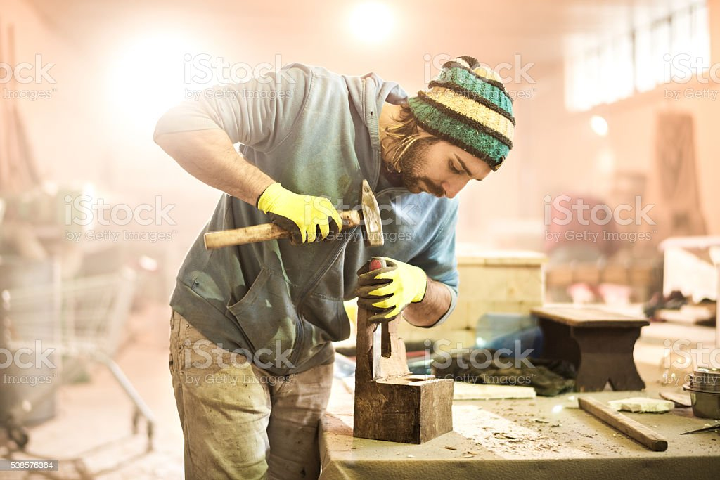 Carpenter with hammer and chisel stock photo
