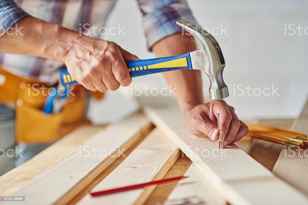 Carpenter with hammer hitting nails stock photo