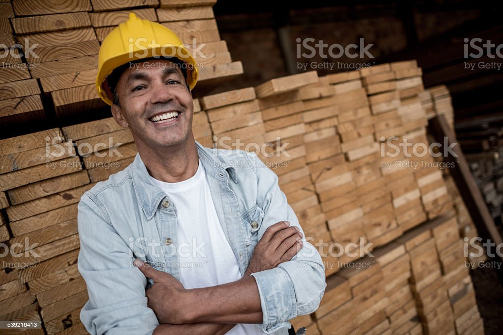 Carpenter with piles of wood stock photo