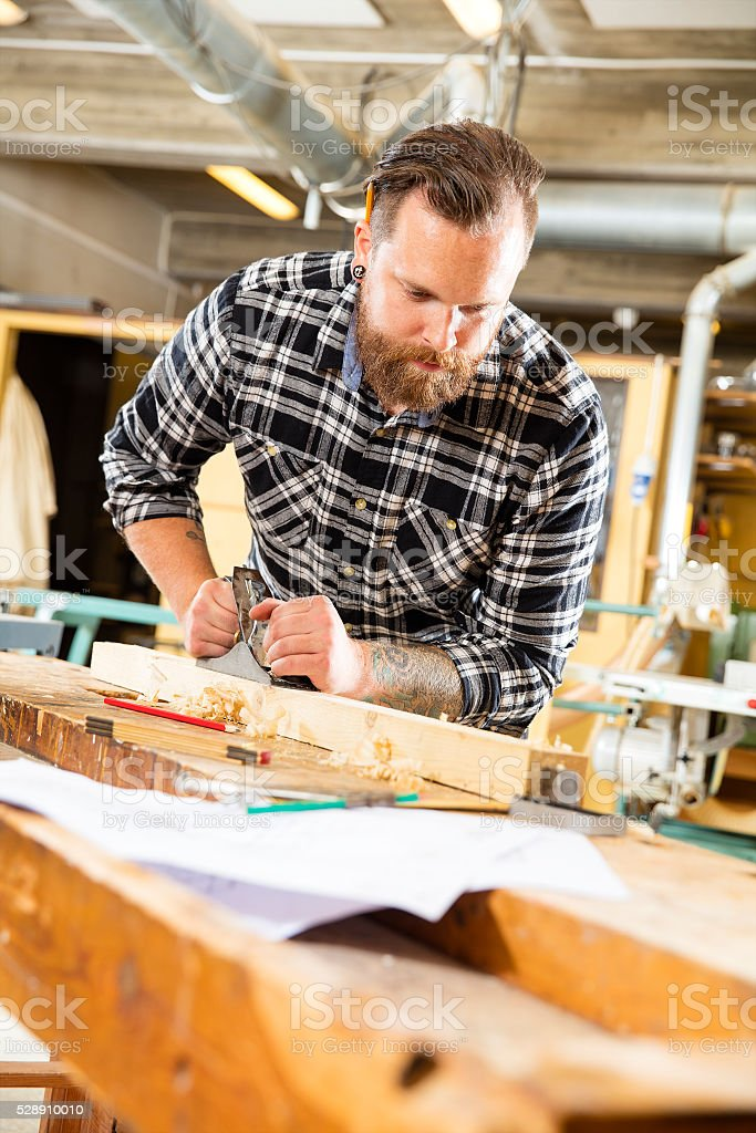 Carpenter work with plane on wood plank in workshop stock photo