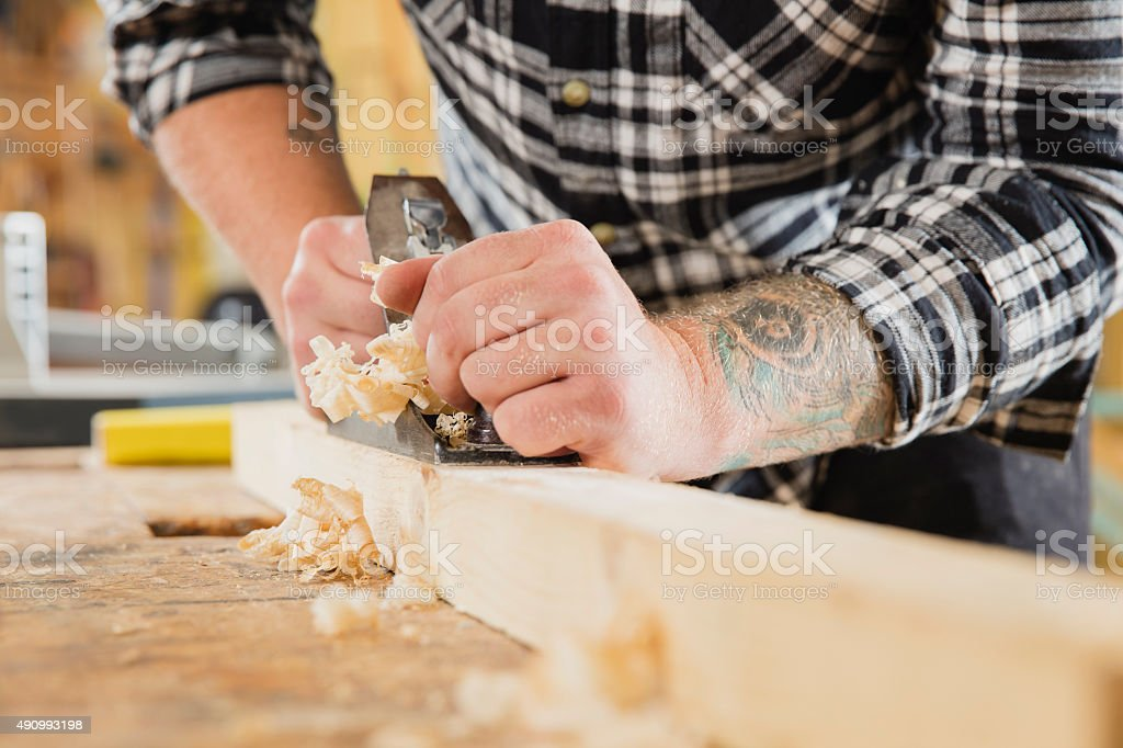 Carpenter work with plane on wood plank stock photo
